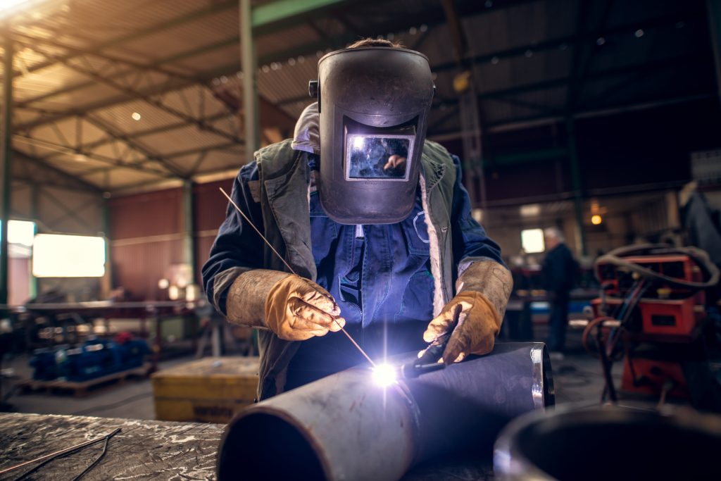worker welding a steel tube